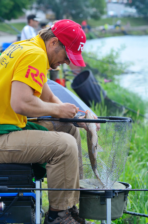 yearly: MINSK, BELARUS - JUNE 29, 2013: Sportsman on annual fishing competition RS Cup. The contest takes place yearly, on the last weekend of June, in the center of Minsk, on the Svisloch river. Its a proffesional fishing contest, in which sportsmen from Bela