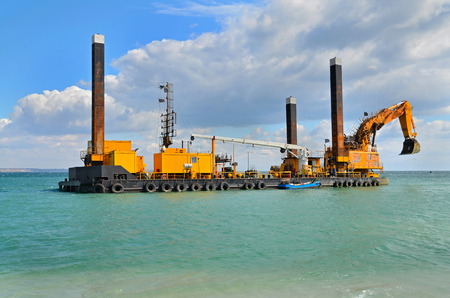 ponton: A large yellow excavator machine construct sea defences on the beach Stock Photo