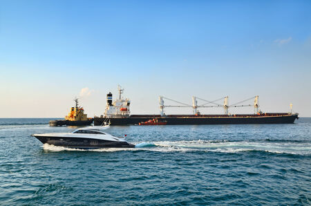 speedboat: Motor yatch, yellow towboat and cargo ship in a sea Stock Photo