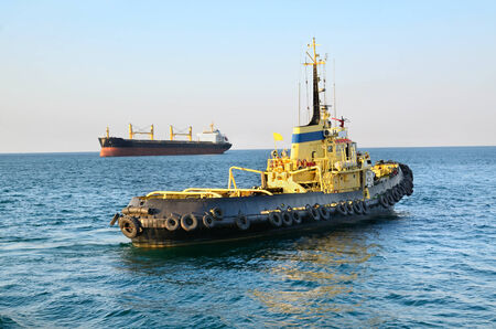 tug boat: Yellow towboat and cargo ship in a harbor