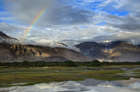 ladakh: Rainbow over Himalayas mountains in Nubra desert valley in Ladakh, India