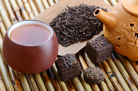 Chinese tea in cup and various black pu-erh tea on bamboo mat background