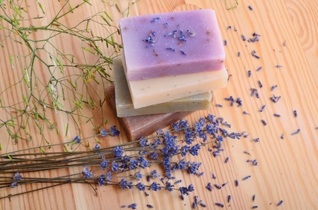 bodycare: Herbal soaps and lavender flowers on a wood background
