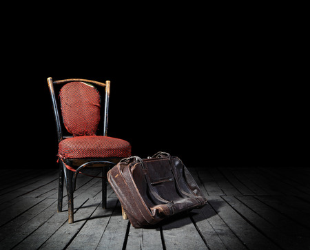 desolation: Old red chair and well-traveled vintage suitcase on wooden floor