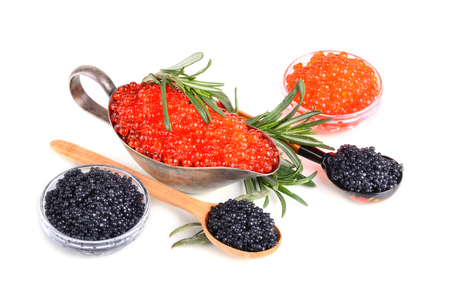 Black and red caviar in glass bowls and in silver sauceboat on a white background photo