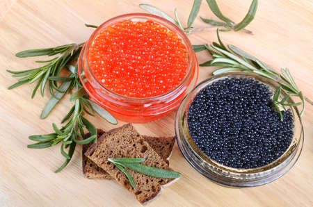 Red and black caviar in glass cans with bread on wooden background photo