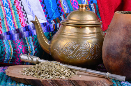 brassy: Cup from calabash and teapot with dry mate leaves.Traditional drink of Peru, Brazil and Argentina.