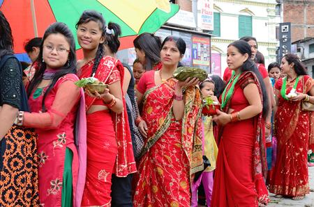kathmandu: Kathmandu, Nepal - September 18, 2012: Hindu women in traditional red sari celebrating the Haritalika Teej festival on the streets of Kathmandu, Nepal