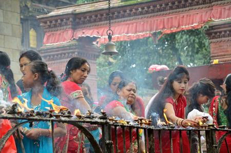Kathmandu, Nepal - September 18, 2012: Hindu women in traditional red sari celebrating the Haritalika Teej festival on Durbar square in Kathmandu, Nepal