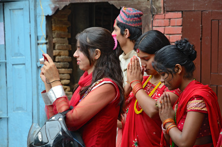 Kathmandu, Nepal - September 18, 2012: Hindu women in traditional red sari celebrating the Haritalika Teej festival and praying on Durbar square in Kathmandu, Nepal