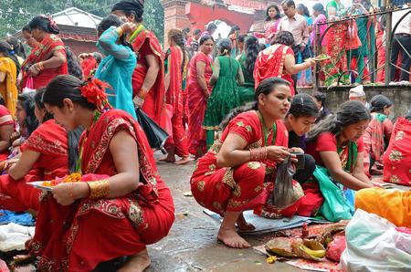 kathmandu: Kathmandu, Nepal - September 18, 2012: Hindu women in traditional red sari celebrating the Haritalika Teej festival and praying on Durbar square in Kathmandu, Nepal