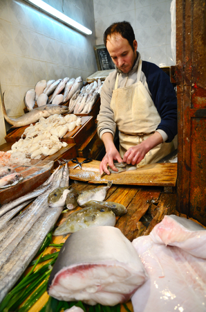 fish selling: Fez, Morocco - March 5, 2014: Traditional moroccan fish store in Fez. Men selling fishes and seafood.