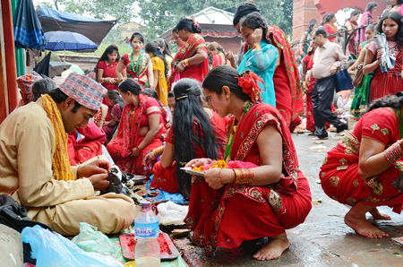 mujeres orando: Katmandú, Nepal - 18 de septiembre de 2012: las mujeres hindúes en sari rojo tradicional que celebra el festival Haritalika Teej y oran en la plaza Durbar de Katmandú, Nepal