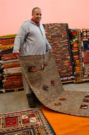 Marrakesh, Morocco - March 12, 2014: Oriental berber rugs in a carpet store in Morocco. The seller shows a carpet to buyers.