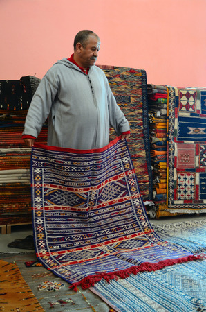 berber: Marrakesh, Morocco - March 12, 2014: Oriental berber rugs in a carpet store in Morocco. The seller shows a carpet to buyers.