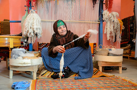 Marrakesh, Morocco - March 12, 2014: Woman spining a woolen string for berber moroccan carpets