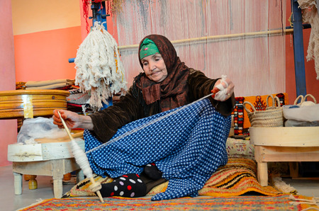 Marrakesh, Morocco - March 12, 2014: Senior woman spining a woolen string for berber moroccan carpets