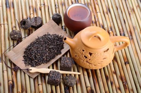 Chinese teapot and various black pu-erh tea on bamboo mat background Stock Photo