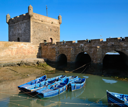 ramparts: Blue fishing boats and historical bastion in Essaouira, Morocco on the Atlantic coast, North Africa.