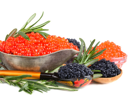 Black and red caviar in silver sauceboat with spoons and rosemary on white background photo
