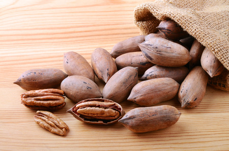pecan: Pecan nuts in a burlap sack bag close up on a wooden background Stock Photo