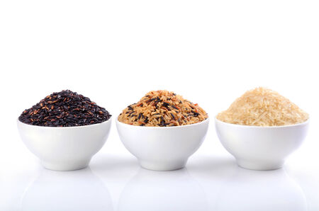 brown rice: White, wild and brown rice in ceramic bowls on white background Stock Photo