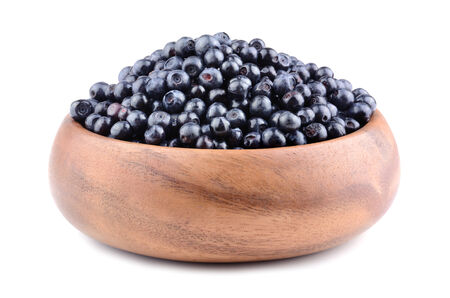 bilberries: Heap of ripe bilberries in bamboo plate on white background