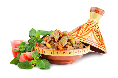Tajine, moroccan national dish full of meat and vegetables with marjoram and tomatoes on a white background