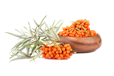 Sea buckthorn berries in bamboo plate isilated on white background