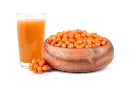 Glass with freshly fruit drink with bamboo plate full of sea buckthorn berries isilated on white background