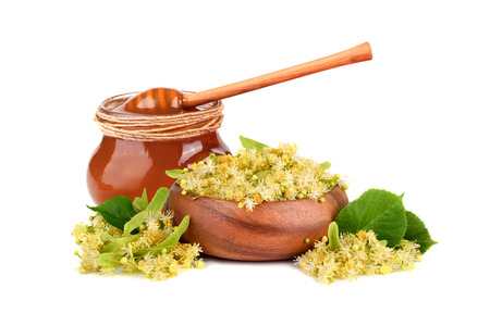 Glass jar fuul of fresh honey with linden flowers in bamboo plate isilated on white background