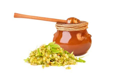 Glass jar fuul of fresh honey with linden flowers isilated on white background