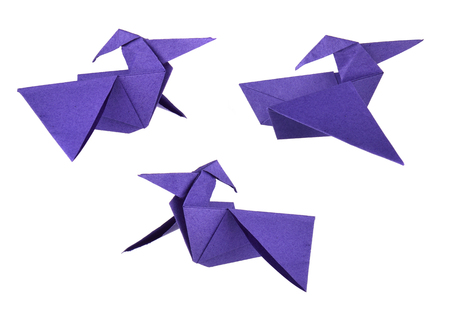 Colored blue origami paper pterodactyls over white background