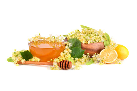 Fresh honey with linden flowers in bamboo plate and lemon citrus isilated on white background Stock Photo