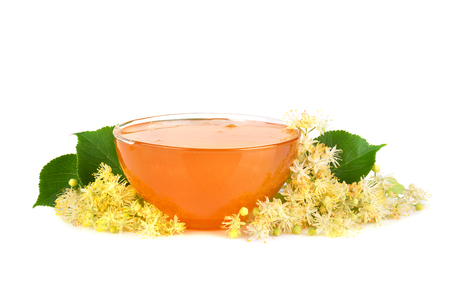 Glass plate full of fresh honey with linden flowers isilated on white background