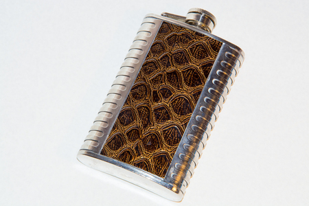 intoxicant: metal flask with leather trim on a white background