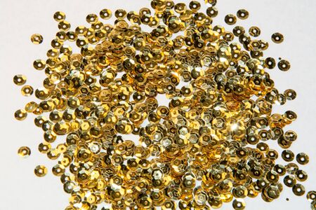 sequins: golden round sequins sewing on a white background Stock Photo