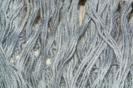 cable knit: The texture of a bundle of gray woolen threads closeup