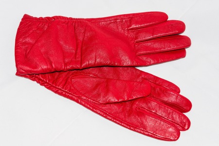 Female red leather gloves close-up on a white background