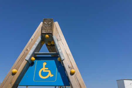 deficient: disabled sign and simbol on wooden swing pole, playground with clear blue sky. pole, playground with clear blue sky.