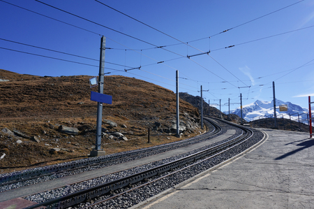 Beautiful scenic train railway transportation on alp with snow mountain in daylight, Switzerland. Stock Photo