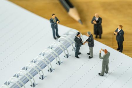 salarios: Gente en miniatura: Pequeños hombres de negocios de la figura apretón de manos y otros que aplauden en cuaderno y lápiz como concepto del acuerdo del negocio.