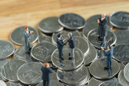 Miniature people: Small figure businessmen handshaking and others clapping on stack of coin as money and financial concept. Stock Photo