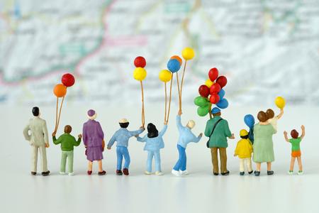 Miniaturleute mit der Familie, die den Ballon betrachtet Karte im Hintergrund als glückliches Familienreisekonzept hält.