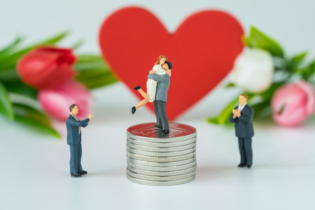 to contemplate: Miniature people with couple standing on top stack of coins and other clapping with the red heart symbol background as success love life concept.