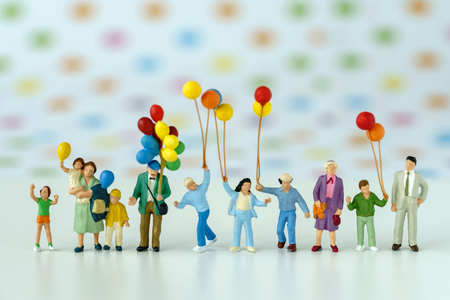 Miniature people with family holding balloon with pop color dot background as happy family concept.
