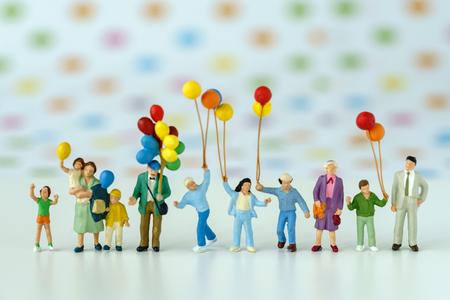 Povos diminutos com a família que guarda o balão com fundo do ponto da cor do PNF como o conceito de família feliz. Foto de archivo