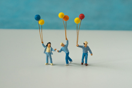 Miniature people with family holding balloon with blue color background as happy family concept. Stock Photo