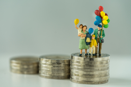 Miniature figure family holding balloon standing on stack of coins as financial business or happy concept.