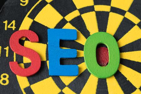 optimisation: SEO Search engine optimization concept as colorful alphabets abbreviation SEO on dartboard.